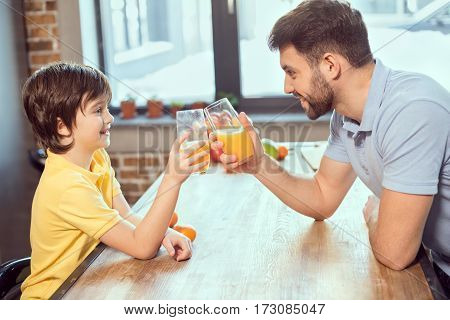 Side view of happy father and son drinking fresh juice together