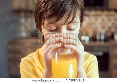 Close-up view of cute little boy drinking fresh orange juice