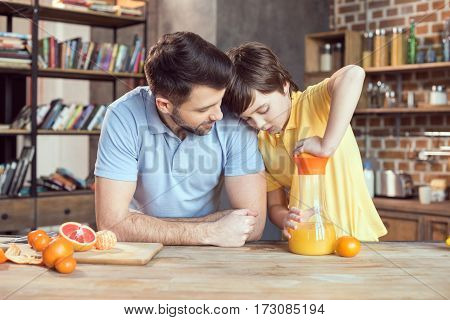 Father and son squeezing fresh orange juice at kitchen table