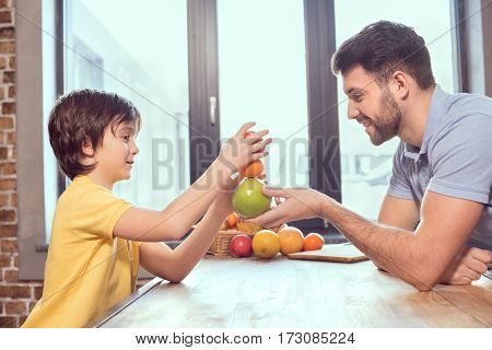 Side view of happy father and son playing with citrus fruits in kitchen