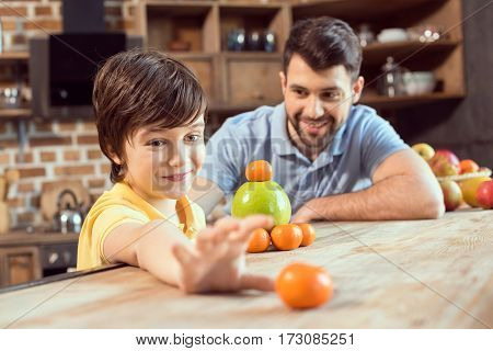 Happy father and son playing with citrus fruits in kitchen