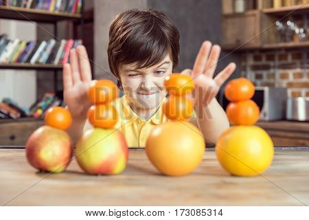 Cute little boy playing with fresh fruits on wooden table