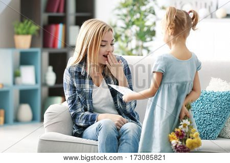 Little girl greeting her mother at home. Mother's day concept
