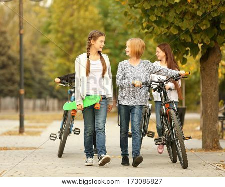 Cheerful friends with bicycles in park