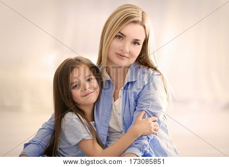 Happy young woman with her daughter at home. Mother's day concept