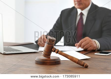 Brown gavel on wooden table and male lawyer on background, close up view