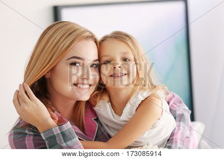 Happy young woman and her daughter at home. Mother's day concept