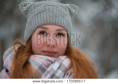 Cute young girl with red hair in winter snow park, telephoto