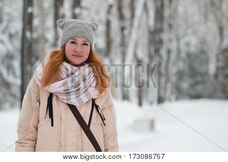 Pretty young girl with red hair in hat standing near snow pines in winter park, vertical