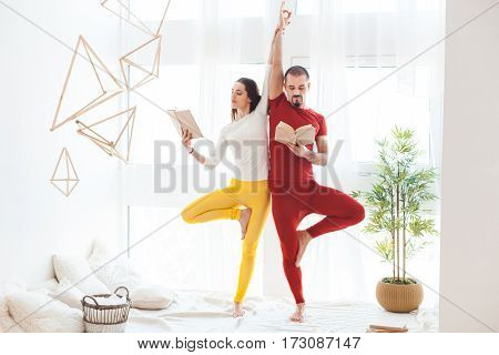 Man and woman doing yoga exercises at home.