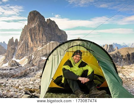 Male mountaineer sitting relaxed in tent and smiling happy after a night outside in the mountains. Great mountain view in background. Alps, Dolomites, Italy.