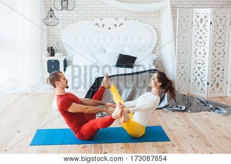Man and woman stretch the muscles while working out in the morning at home.