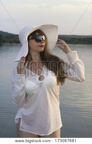 white woman in sun hat posture on beach lake summer day