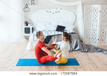 Young people doing sport exercises in the morning in the bedroom.