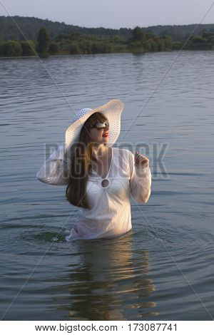 white woman in sun hat posture on lake summer day