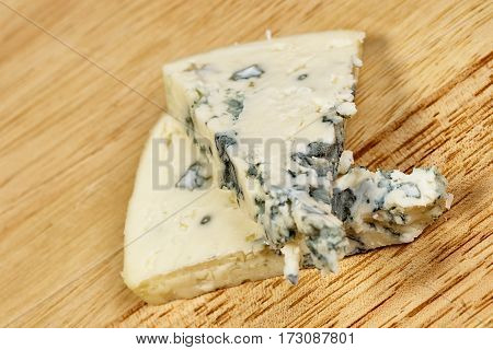 Blue cheese close up on an old wooden table and a knife horizontal macro mold