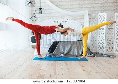 Man and woman doing morning exercises in the bedroom.