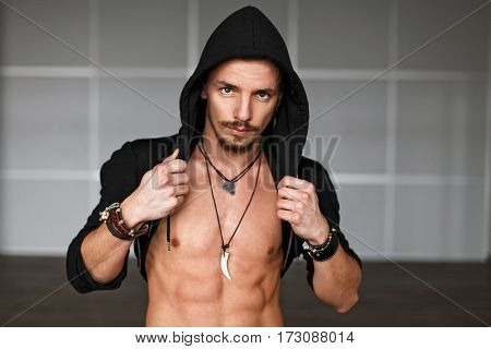 Portrait Of A Handsome Male Dancer In Black Clothes Near The Wall