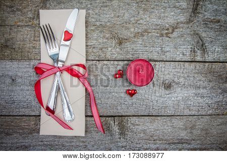 Red Candle, Fork And Knife On Old Rustic Wooden Table