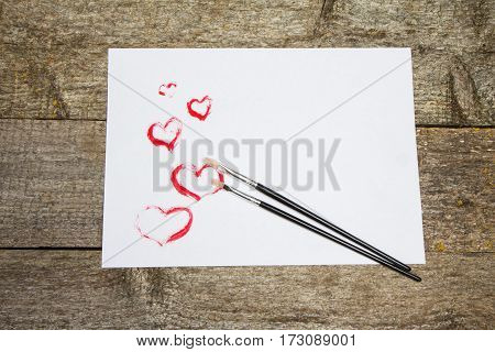 Hearts Drawn On White Sheet Paper And Brush On Table