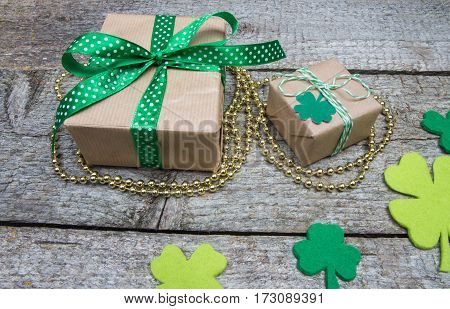 Two Gift With Green Ribbons, Beads And Golden Clover Leaves On Table