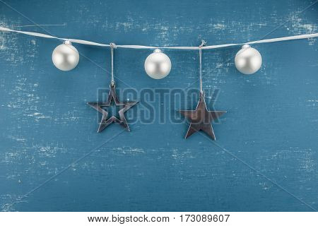 White and Metal Ornaments hang from ribbon
