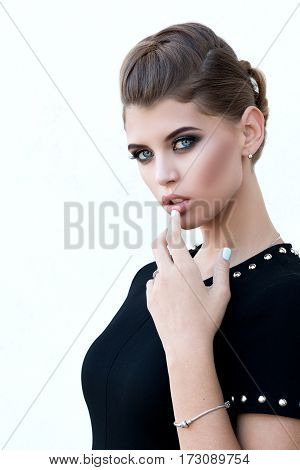 Beautiful Girl With Make-up And Hairdo Finger Pulls The Lip, Isolated On Light Background