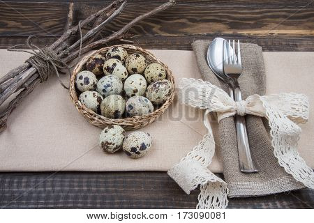 Cutlery, Quail Eggs And Twigs On Brown Table With Beige Cloth