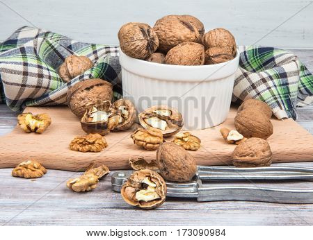 Walnuts, Nutcracker, White Bowl And Checked Towel On Wooden Background
