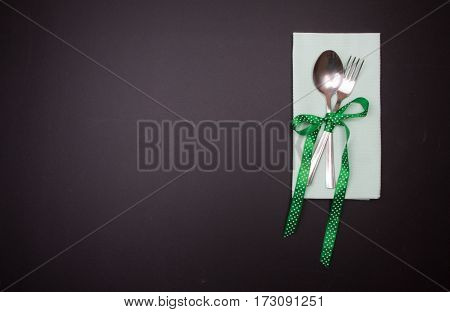 Spoon And Fork Tied With Green Ribbon With Dots On Blackboard