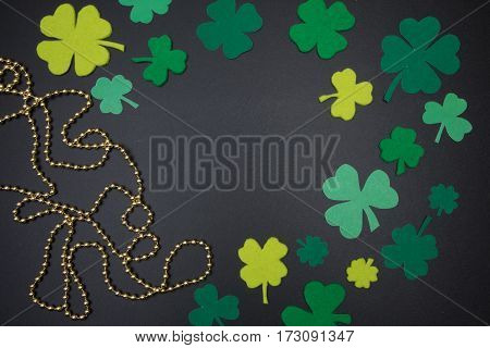 Leaves Of Clover And Golden Beads On Chalkboard. St. Patricks Day