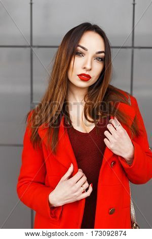 Young Beautiful Girl In The Red Coat On A Gray Background