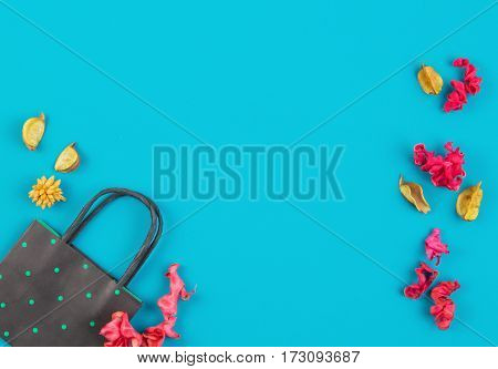 Black and green polka dot paper shopping bag and colorful dried flowers plants on blue background. Top view, flat lay. Copy space for text