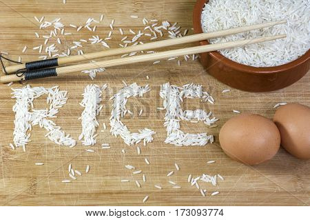 White basmati rice with chopsticks and two brown eggs on the light wooden background
