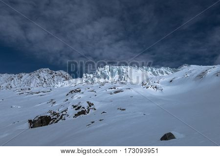 Part of Glacier du Tour with seracs ice blocks crevasses illuminated by sunlight through clouds in a vast winter landscape horizon in the Alps