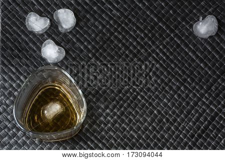 One glass of bourbon with ice on black leather background