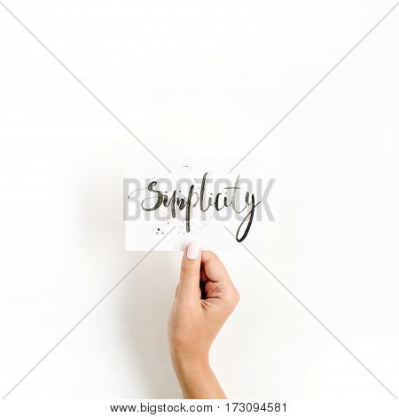 Minimal pale composition with girl's hand holding card with word Simplicity written in calligraphic style on paper on white background. Flat lay top view
