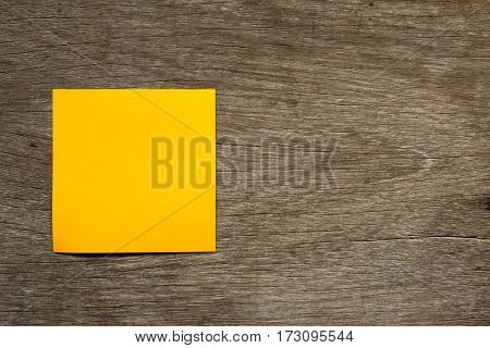 Blank orange note paper attach on brown wooden background for memo or remind