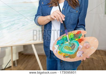 Partial view of woman artist holding paintbrush and palette while painting picture