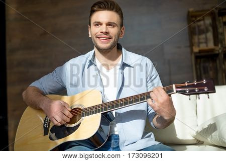 Handsome smiling young man playing guitar and looking away