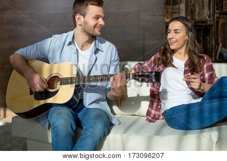 Happy young couple with guitar sitting on sofa and looking at each other