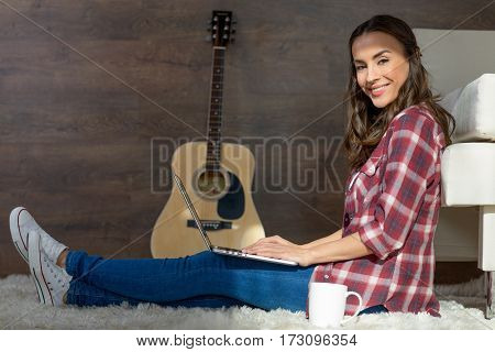 Attractive young woman using laptop while sitting on carpet and smiling at camera