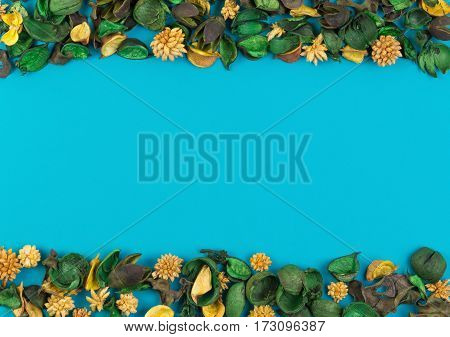 Dried flowers and leaves border frame on blue background. Top view, flat lay