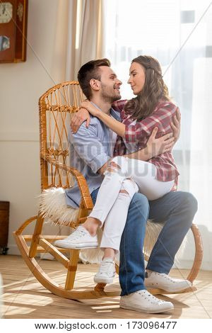 Happy young couple hugging in rocking chair and looking at each other