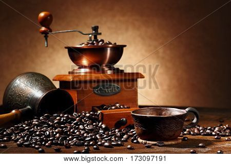 still life with coffee beans and old coffee mill clay cup and turk on the wooden background.