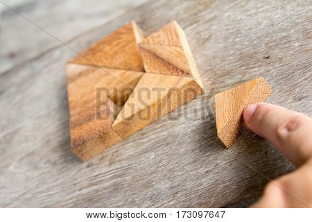 Tangram in heart shape wait for fulfill to complete on wooden background