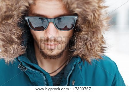 Handsome Man With A Mustache And Beard In A Warm Winter Jacket With Sunglasses On A White Background
