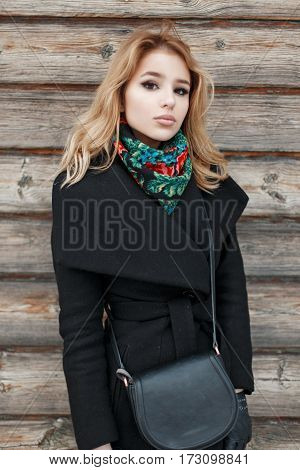 Fashion Beautiful Blonde Woman In A Stylish Black Coat With Bag Standing Near A Wooden Wall