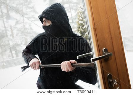 house robbery - robber trying open door with crowbar