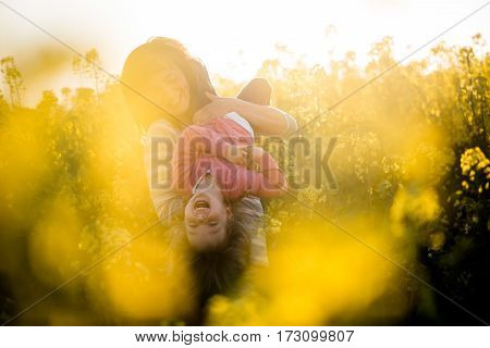 Mother holding baby girl upside down in a rapeseed field. Fun day outdoors.